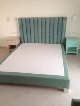 Κρεβάτι ντυμένο και κομοδίνα σε χρωματιστή λάκα σε ξενοδοχείο της Χαλκιδικής